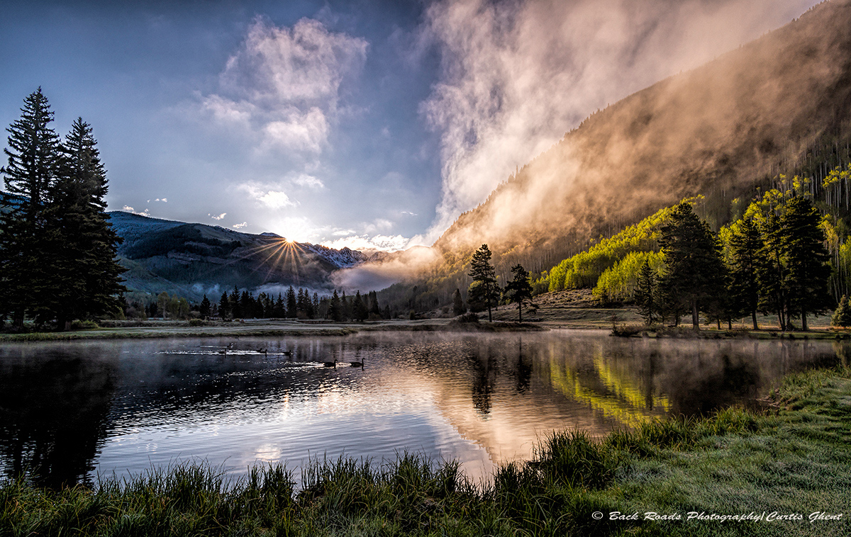 Morning fog rising from the valley as the sun just peeks over the Gore Range.