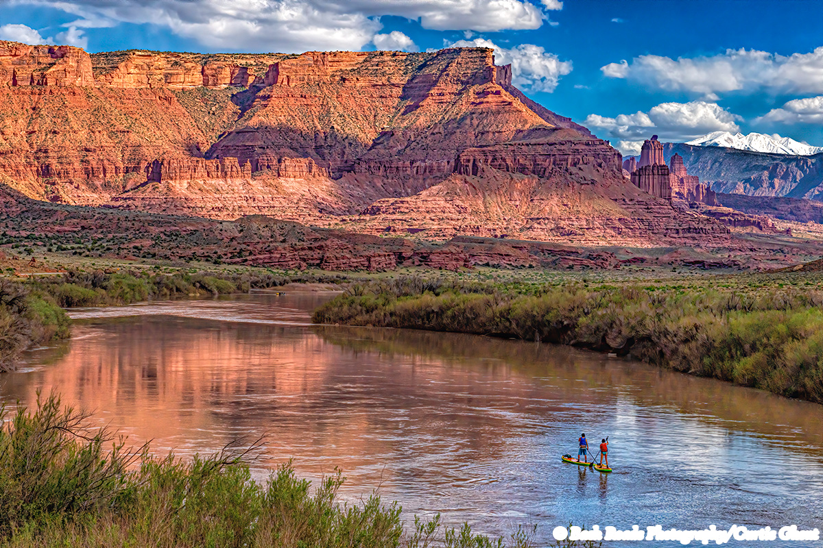 Two stand up paddle boarders enjoying a trip down the Colorado River with the Fischer Towers in the background.