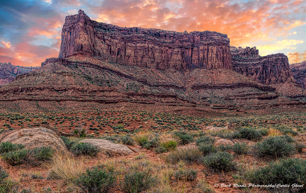 Colorful sunset clouds highlight one of the many buttes on the White Rim.